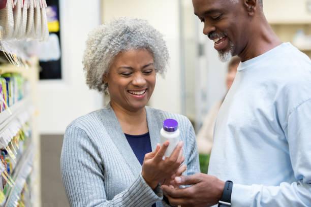 senioren lesen medizin flasche etiketten in apotheke oder supermarkt - lieblingsrezepte stock-fotos und bilder