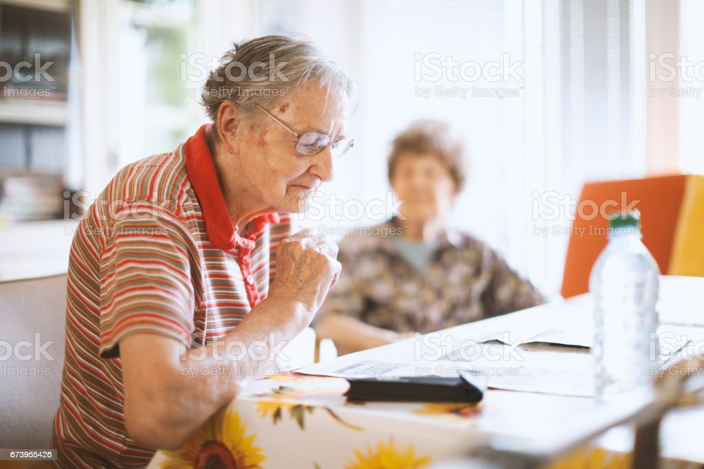 Seniors Reading Newspaper  In The Nursing Home stock photo