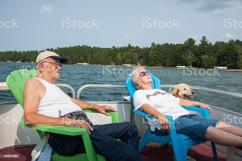 Seniors relaja en un bote de pontones - foto de stock