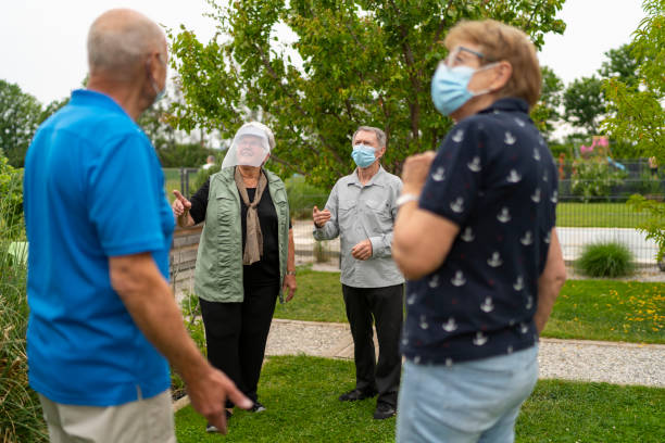 seniors, retirees, people of vulnerable group, chatting in garden back yard stock photo