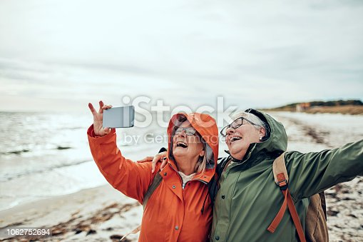 Close up of two female seniors taking a selfie by the beach