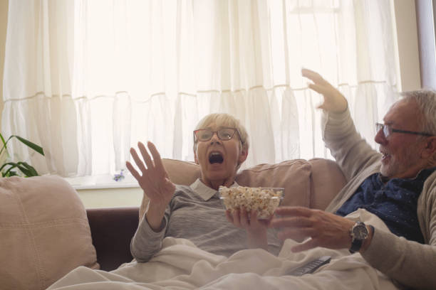 Seniors Shocked by TV. Shocked senior couple watching tv show eating pop corn. gasping stock pictures, royalty-free photos & images