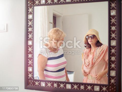 Seniors showing a new dress in front of a mirror