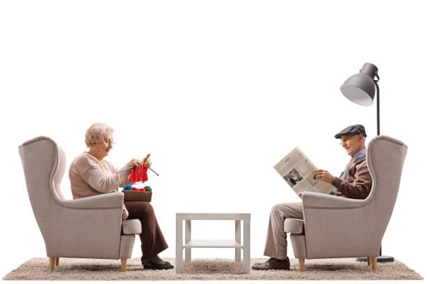 senioren im sessel mit einem von ihnen sitzen stricken und andererseits eine zeitung lesen - basteln mit zeitungspapier stock-fotos und bilder