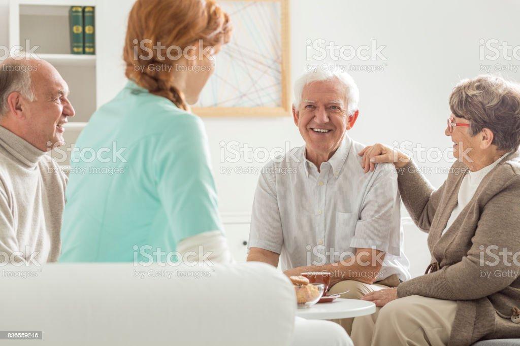 Seniors sitting with nurse stock photo