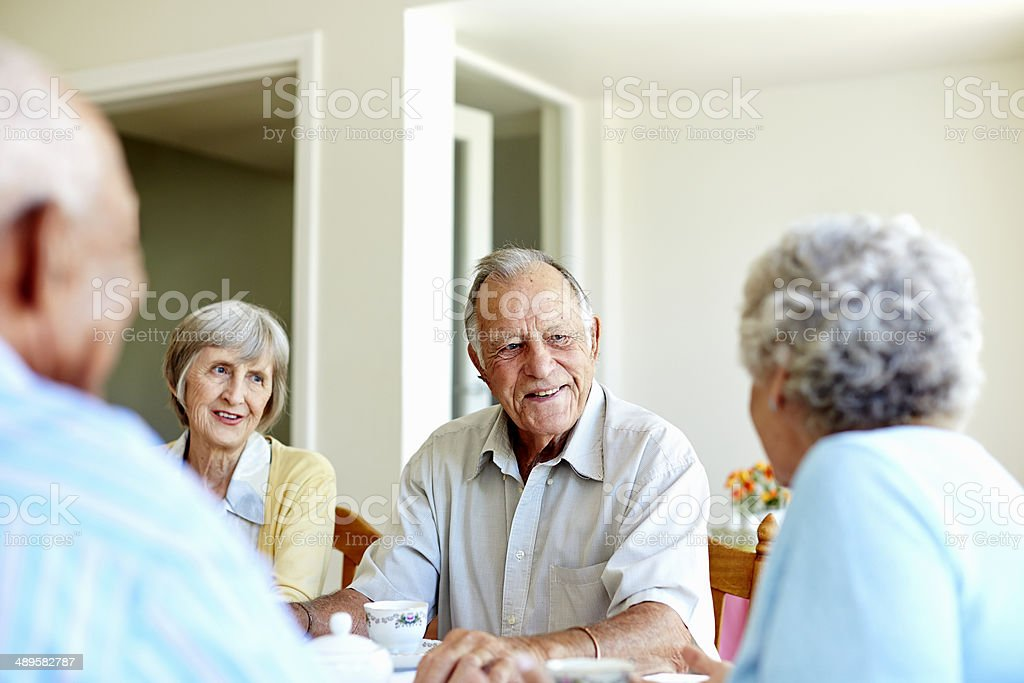 Happy senior people spending leisure time at table in nursing home