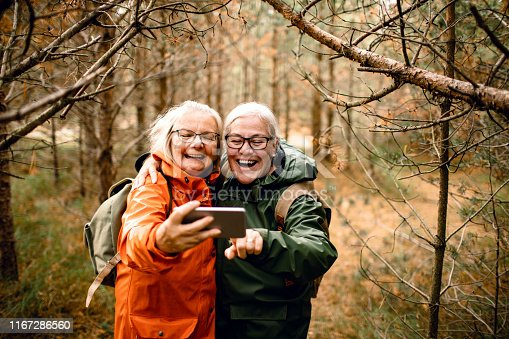 Close up of two female seniors taking a selfie while hiking in the forest