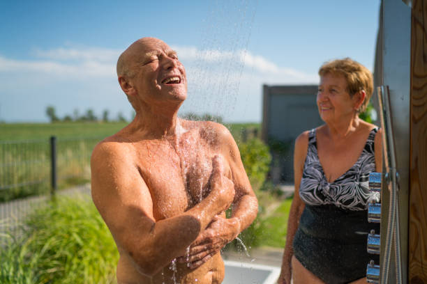senioren - unter der dusche zu hause im garten - sonnendusche stock-fotos und bilder