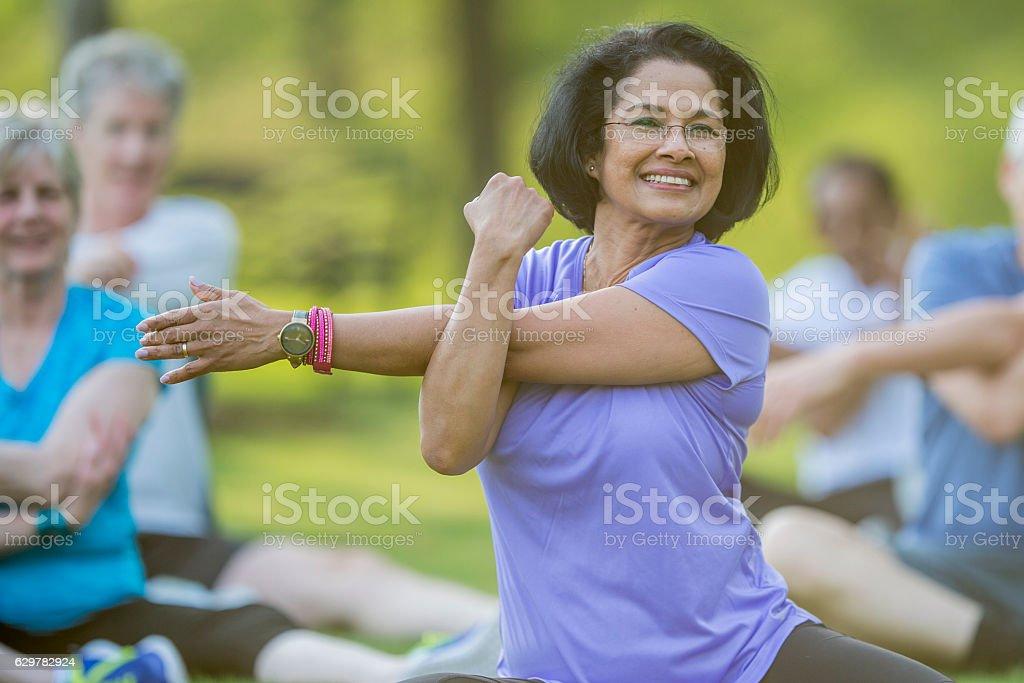 Seniors Taking an Outdoor Fitness Class stock photo