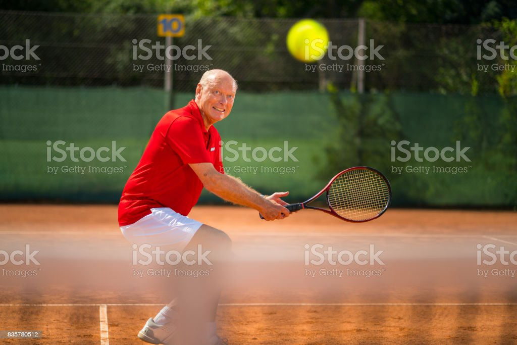 Seniors Taking on the World, 70 years old tennis player volleying on net stock photo