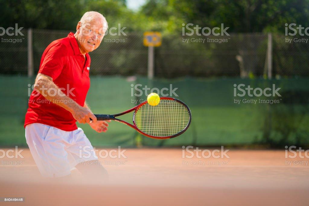 Seniors Taking on the World - 73 years old man volleying tennisball on net stock photo
