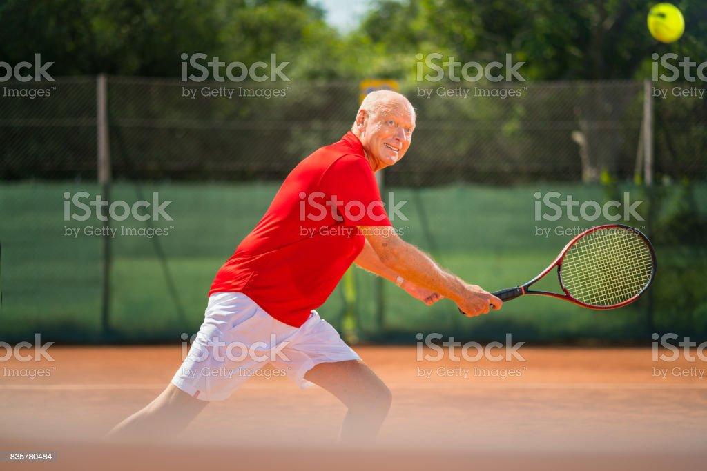 Seniors Taking on the World, active senior man playing tennis stock photo