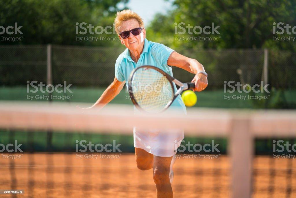 Seniors Taking on the World, active senior woman tennis player volleying on net stock photo