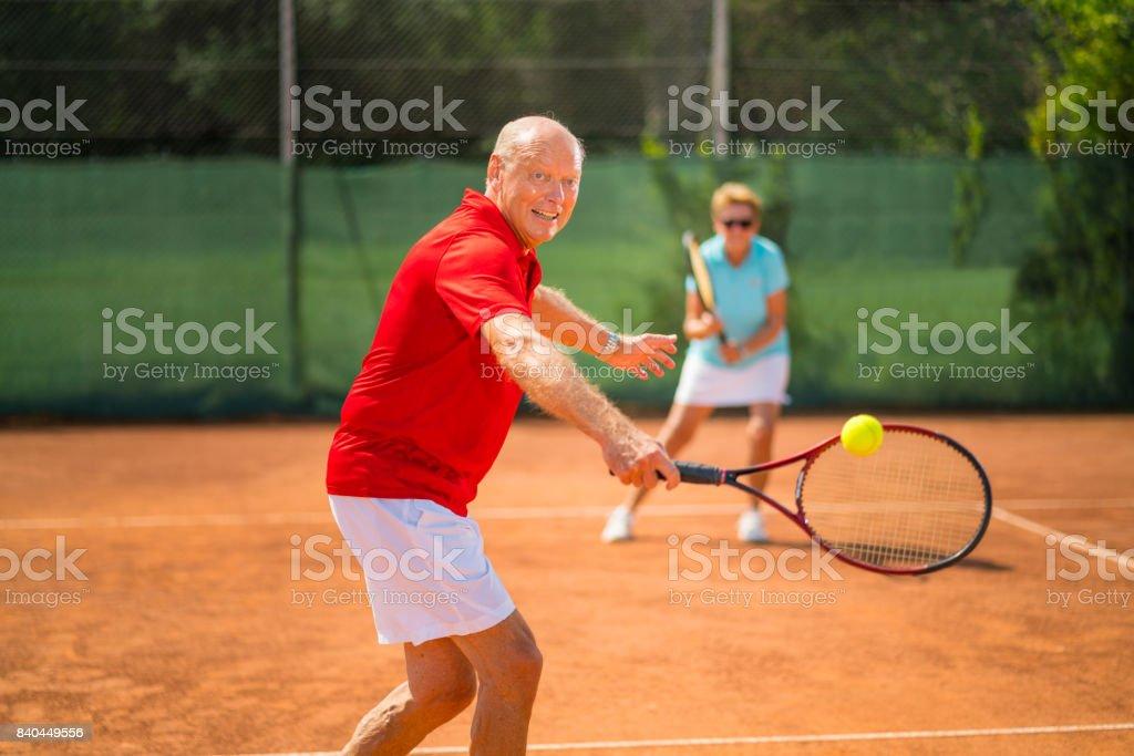 Seniors Taking on the World, couple playing tennis double stock photo