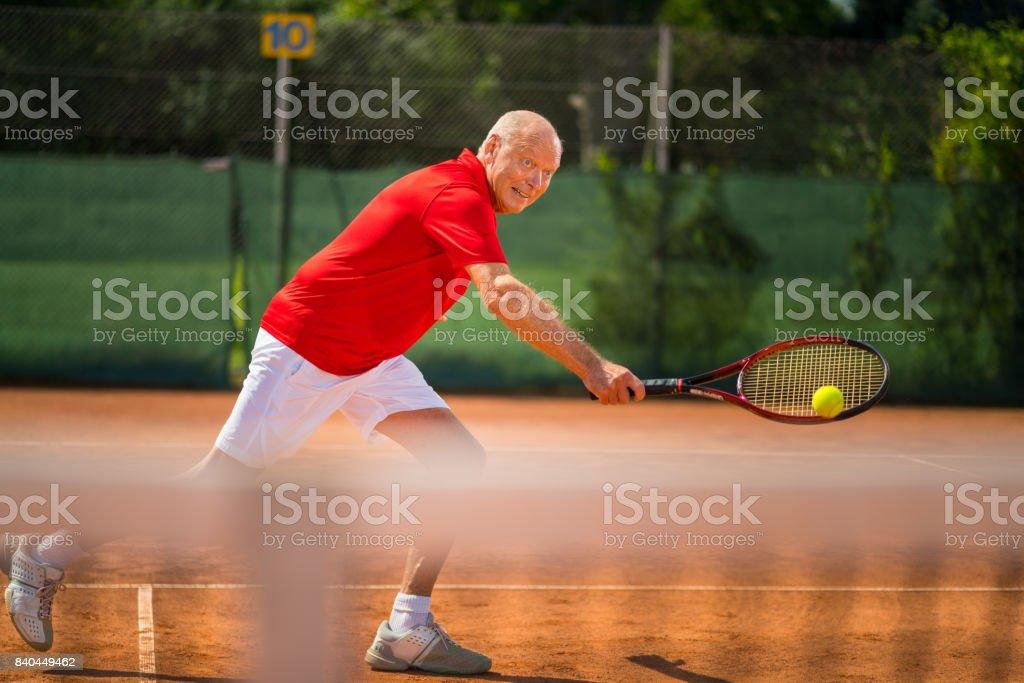 Seniors Taking on the World, fit senior man playing tennis stock photo