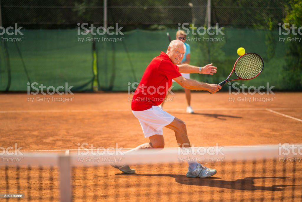 Seniors Taking on the World, happy contcentrated senior tennis player stock photo