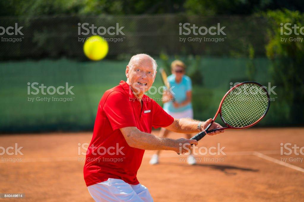 Seniors Taking on the World, happy senior man volleying on tennis net stock photo