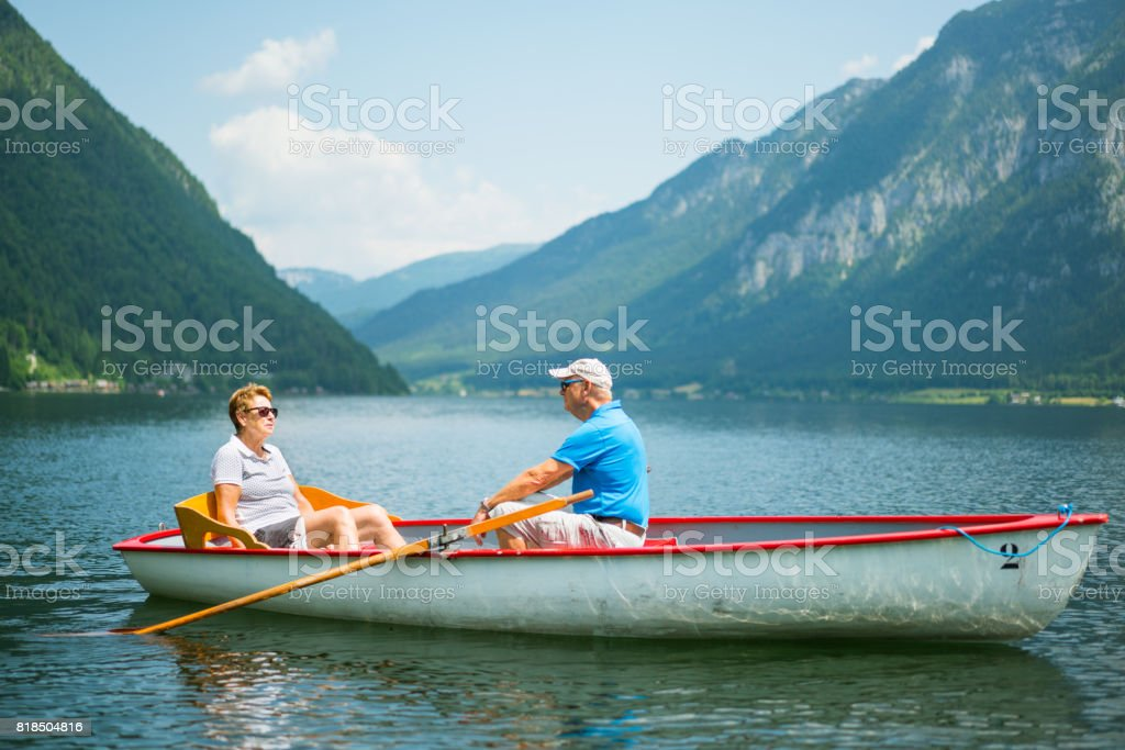 Seniors Taking on the World, in row boat on lake in mountains stock photo