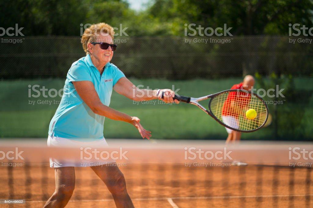 Seniors Taking on the World, senior adults playing tennis stock photo