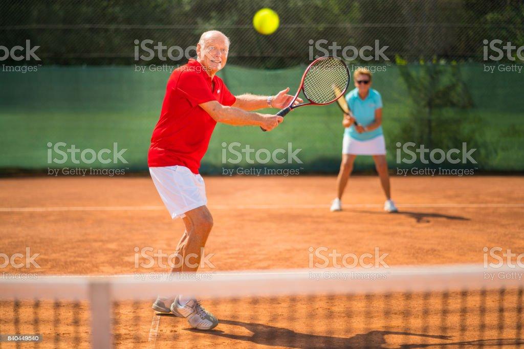 Seniors Taking on the World, smiling senior tennis player focusing ball on net stock photo