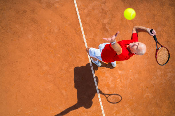seniors taking on the world, tennis service from above - racket sport stock pictures, royalty-free photos & images