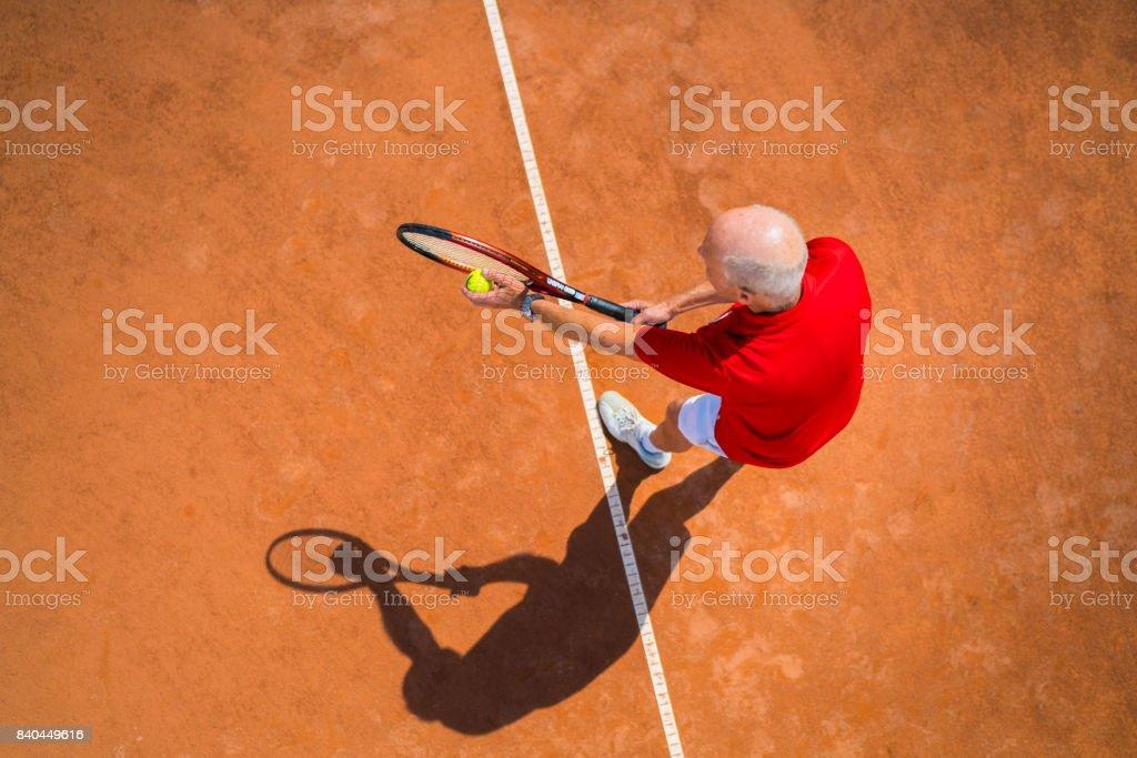 Seniors Taking on the World, top view senior man tennis service stock photo