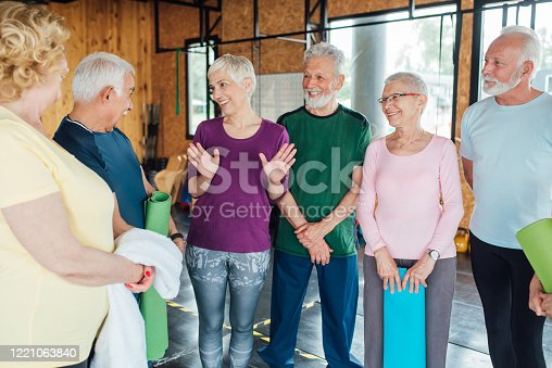 1047537292 istock photo Seniors talking and enjoying together before their group yoga class 1221063840