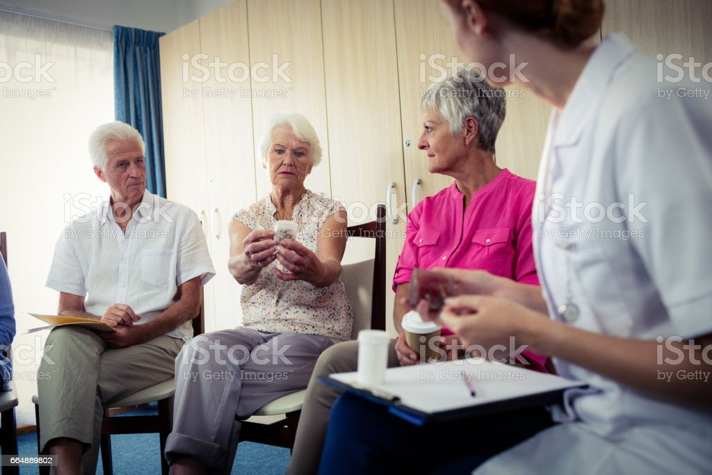 Seniors talking with nurse about medication foto stock royalty-free
