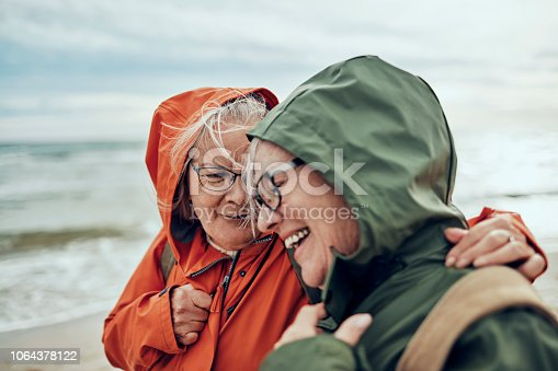 Close up of two female seniors having a walk by the beach