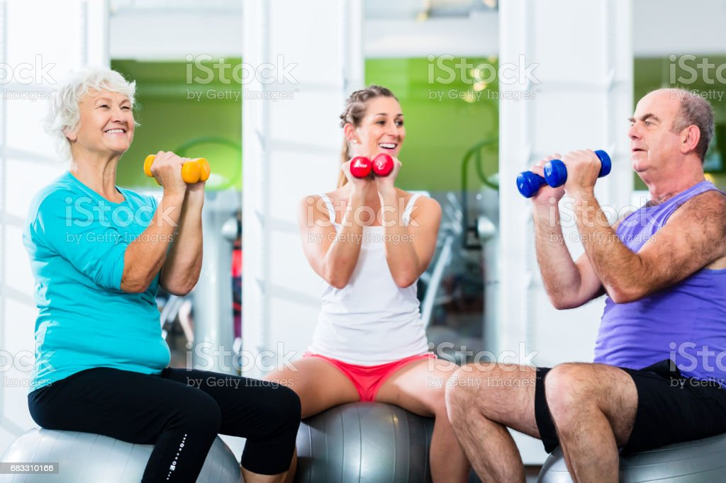 Seniors with trainer in gym at sport lifting barbell foto stock royalty-free