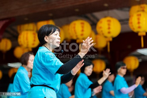 Seniors woman leads group of Tai Chi students using a microphone.