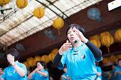Seniors woman using microphone leading group of senior Tai Chi students.