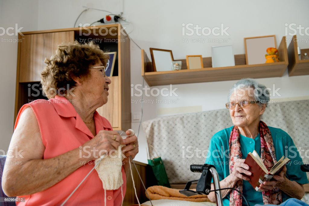 Seniors Women Socializing In The Bedroom At The Nursery Home stock photo