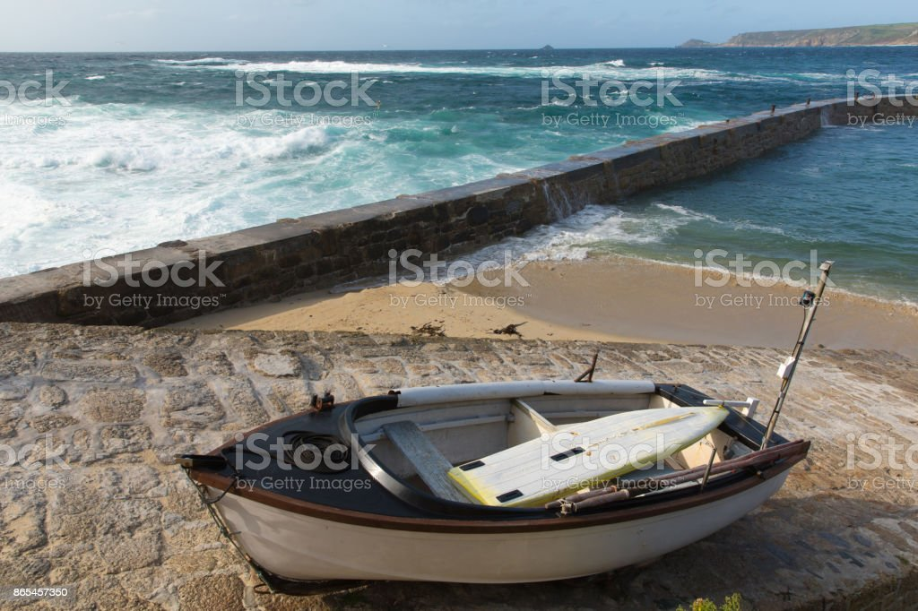 Sennon Cove Cornwall rowing boat and harbour wall with blue sea and waves stock photo
