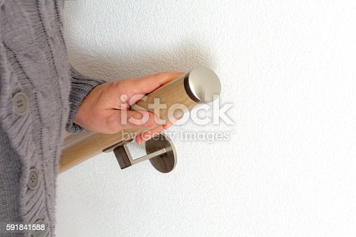 senior  in a knitted gray buttoned cardigan  holding on to wooden handrail while going down the stairs focus on hand