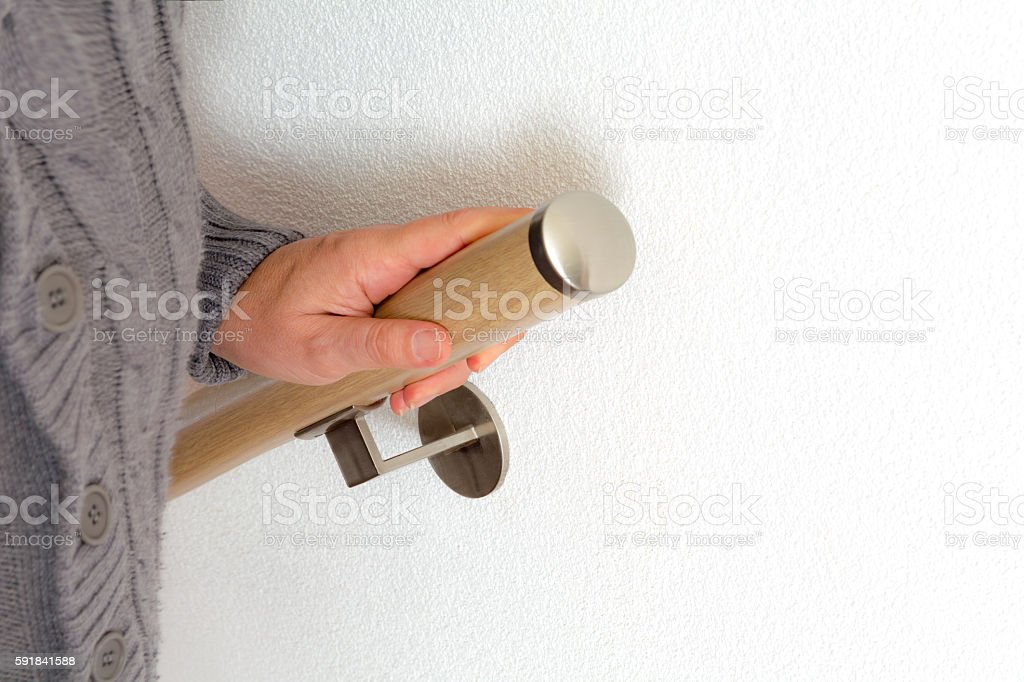 senoir holding on to wooden handrail going up the stairs stock photo