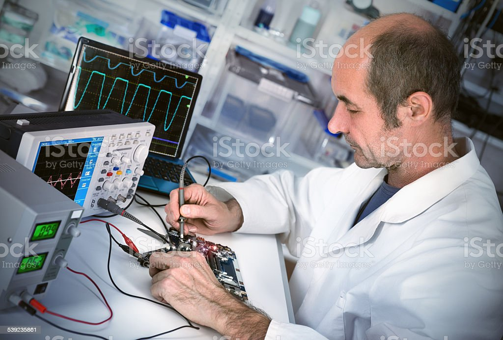 Senor male tech fixes motherboard in computer repair shop royalty-free stock photo
