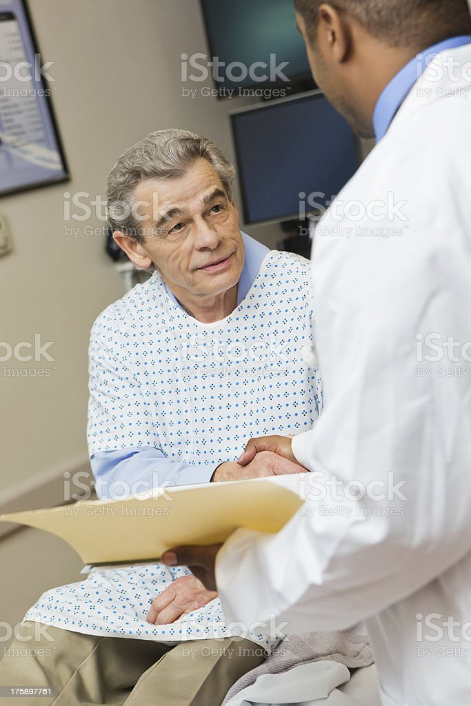 Senor patient talking with doctor in hospital emergency room