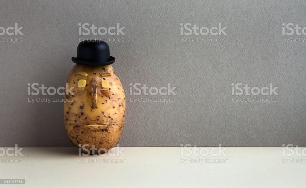 Senor Potato bowler hat serious face. Old fashioned style vegetable on gray wall background. Copy space stock photo