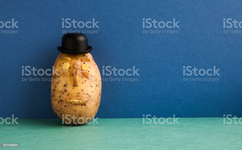 Senor Potato bowler hat serious face. Old fashioned style vegetable on blue wall green floor background. Copy space stock photo