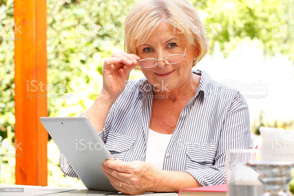 Senor woman with diigital tablet stock photo