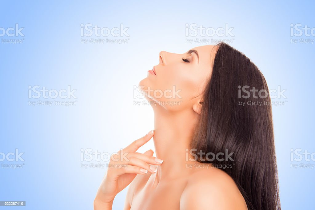 Sensitive relaxed woman touching her neck on blue background stock photo