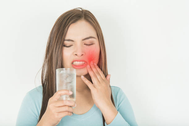 Sensitive teeth in woman And a glass stock photo