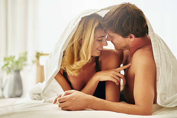 Sensitive to her touch Shot of a young couple sharing an intimate moment under the covers in bed real couples making love stock pictures, royalty-free photos & images