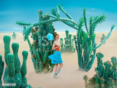Woman is a sensitive being. Woman with balloons in a field of cactus.