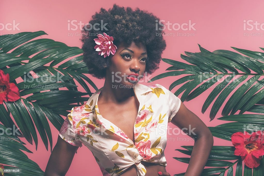 Sensual Afro American Pin-up Between Palm Leaves. Against Pink Background. stock photo