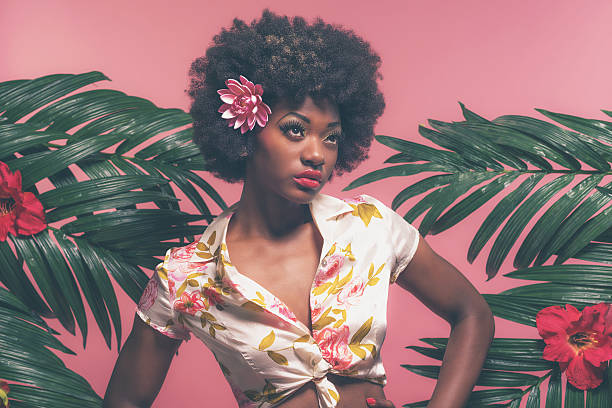 sensual afro american pin-up between palm leaves. against pink background. - pin up girl stock pictures, royalty-free photos & images