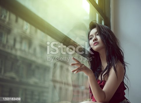 506435758 istock photo Sensual asian young woman sitting by the window, looking out, emotional portrait 1203183459