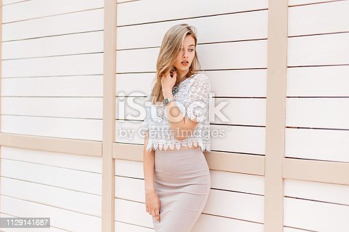 578791454istockphoto Sensual attractive young woman in a beige elegant skirt in a vintage lace blouse posing near a white wooden wall outdoors on a warm spring day. Pretty girl on vacation. 1129141687