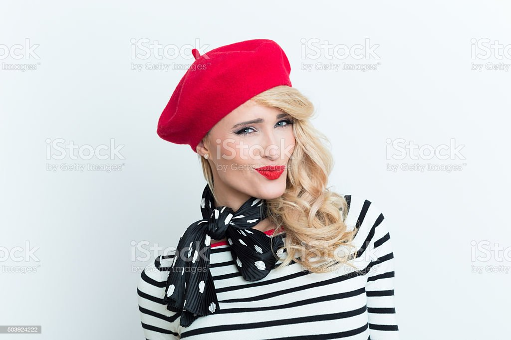 Sensual blonde french woman wearing red beret Portrait of sensual blonde woman in french outfit, wearing a red beret, striped blouse and neckerchief, smirking at camera. Adult Stock Photo
